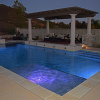 20' x 40' rectangular pool with travertine coping, light gray plaster with a raised sitting deck and Pacific Stone precast columns/wood patio cover. Pentair 5G LED color changing lights.