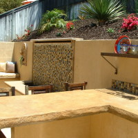 Tiled Waterwall and seatbench. Textured and acid stained BBQ counter