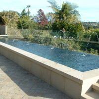 "Precast concrete coping and raised wall clading and steps. Belgard paver decking. Pool is raised +18"" for a seat wall effect."