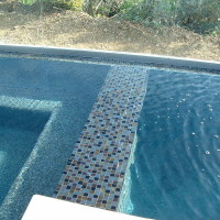 Oceanside glass spa spillwall and black pearl pebble.