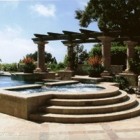 Large grecian spa with travertine coping and sides and landing steps.