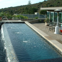 Oceanside glass tiled 0-edge spillwall with glass panel fencing, precast concrete coping.