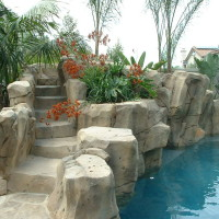 Lighted artificial rock slide steps with pocket planters in waterfall and grotto to create a natural effect.