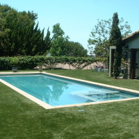 Tuscan rectangle with automatic pool cover, precast concrete coping stones, glass tile, and artificial turf lawn.