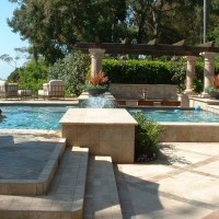 """+18"""" rasied pool with raised deck areas. Travertine coping and oceanside glass tile. Travertine and slate patterned decking."""