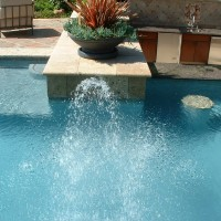 Water spray heads coming out of a raised travertine deck pedestal.