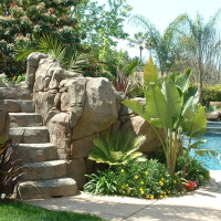 Artificial rock water slide, grotto, and waterfalls. Lighted access steps, landscaped pocket planters