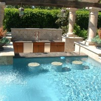 Swim up granite top counter bar with in-pool stools and a sunken bar serving area with refrigerator, sink, serving counter all at proper service height.