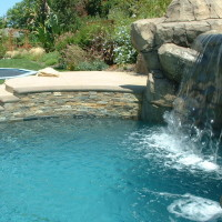 Stacked quartz and poured in place concrete coping. Waterfall/ grotto.