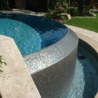 Oceanside glass tile on the o-edge spillwall. Travertine coping with light grey plaster and blue 3M color quartz.