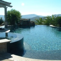 Freeform pool with raised spa , small natural waterfall.0-edge spill wall, travertine coping with glass tile.