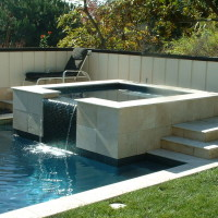 Raised spa with travertine coping and wall face. Oceanside glass tile.