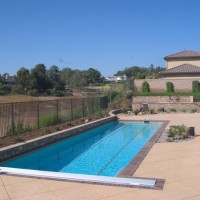 Lap pool with auto cover, bullnose bricks, raised back pool wall.