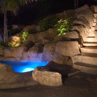 Artificial rock spa and waterfall with lighted pocket planter and steps to the 30' water slide. Rock decking is acid stained and rock textured to resemble natural stone.
