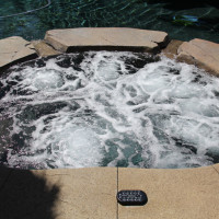 Custom spa with swim-up bar, room for 8. Rock textured colored concrete with acid stain.