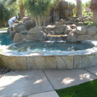 Large kidney shaped spa raised with quartzite natural stone. Artificial rock waterfalls.