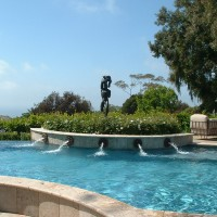 Statue of Olympus in a raised travertine pool planter surrounded by (5)ornamental spray head sconces, Oceanside glass tile, light gray plaster. Description 	: 	Geometric Custom Raised Pool