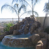 Raised spa with quartzite coping and natural boulders.