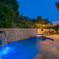 yard was expanded by 12'. Stacked ledger stone retaining wall ties into pool and spa with faux rock waterfall/grotto. Pacific stone coping and belgard paver decking.