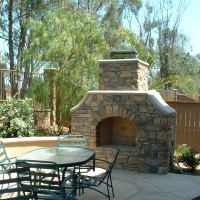 Cultered stone and poured in place concrete caps accent this medium sized fireplace and decking area.