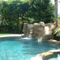 Rock slide and waterfall with walk-in cave, quartz coping, lush landscaping.