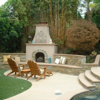 Outdoor fireplace with stacked quartzite and poured in place colored concrete hearth and wall cap