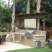 Stacked quartz BBQ with trellis overhead and poured in place concrete counter top and cap