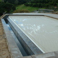 Automatic pool cover track is mounted to the o-edge spiilwall.