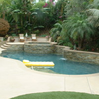 Pool with stacked ledger stone wall and spa. Poured in place colored concrete deck and coping