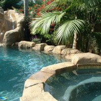Artificial rock boulders with seat ledges on raised back pool wall. Various colors selections and tones are available.