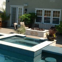 Rasied spa with double sided bullnose travertine coping and glass tile. Glass tiled counter bar with in-pool bar stools.