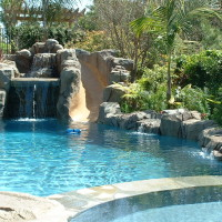 Artificial rock water slide and grotto with jumping rocks and waterfall. Rock boulder coping on back pool wall.