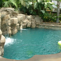 Manmade rock waterfall. Colored plaster adds a unique color to the water. Tropical lanscape fits in nicley.