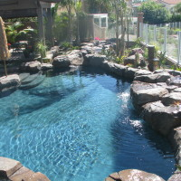 Small freeform lagoon style pool and spa with landscape boulders, waterfall/ stream, baja landing with umbrella boulder. Gemstone interior pool finish.