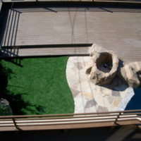 Synthetic grass area with flagstone patio and synthetic rock firepit.