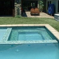 Glass tile spa wall, steps, and benches. Artificial turf around entire pool.