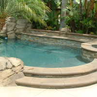 Pool with stacked quartz raised wall and spa and poured in place concrete steps and coping