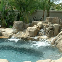 Artificial rock waterfall into raised spa.