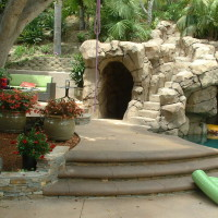 Entrance to artificial rock grotto cave and steps to slide and jump boulders