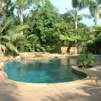 Natural freeform pool and spa with light colors including quartzite coping, artificial faux rock waterslide and walk-in cave/grotto with 5' tall x 5' wide cascading waterfall. 6' tall jumping boulders. Mini pebble by Gemstone Pools, inc.