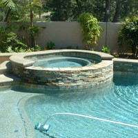Raised spa with poured in place textured multi-color acid stained coping and stacked quartz veneer.
