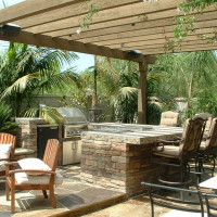 BBQ and bar system with granite counters, flagstone decking, wood patio cover.