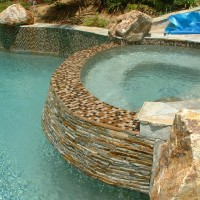 Stacked and slightly angled quartzite spa wall with glass tile top. Pebble aggregate interior finish.