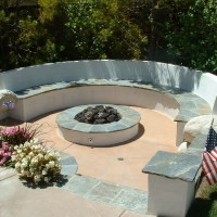 Sunken fire pit area with quartz /stucco seat wall and columns, and steps.