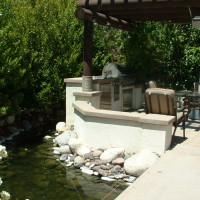 BBQ, fireplace, and Dining area under a large beamed patio structure. (2) bridges give access over the koi pond.