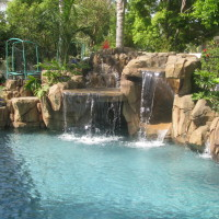This smaller waterfall and slide project has all the elements.Waterfall grotto, jumping boulders, walk-over slide, boulder coping on raised wall, pebble aggregate interior pool finish