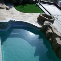 New synthetic grass area, flagstone patio, artificial rock wall and newly surfaced swimming pool.