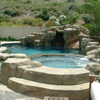 Tropical pool, spa, waterfall, slide, and grotto carved in artificial rock. Beach entry to lagoon style baja shelf with small 4' wide opening into pool to keep the little kids safe and secure. Raised spa and waterfall.
