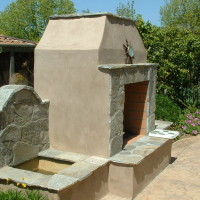 Fireplalarge counter space in BBQ and Bar area for entertainmentce and fountain with stucco finish and quartzite accents.