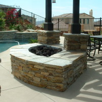 Quartz fire pit and post columns with an open beam shade patio cover.